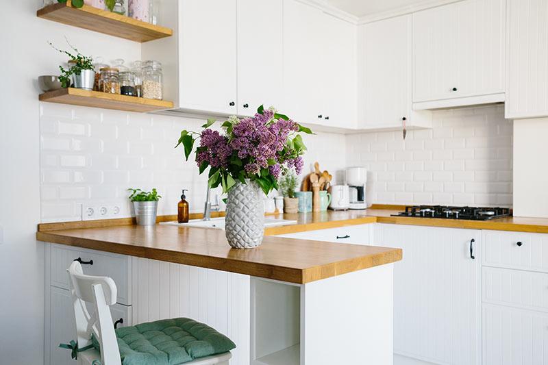 Piccola cucina ad U con penisola, bianca e rovere.