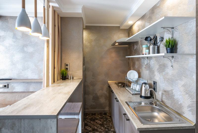 Cucina stretta e lunga ben arredata con penisola e top in granite.