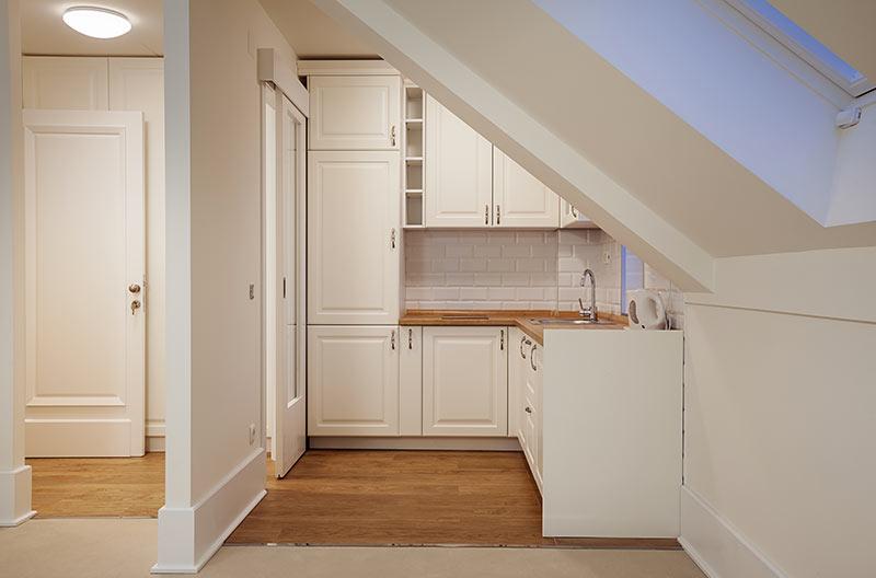 Monolocale con piccola cucina ad angolo bianca con top in legno.