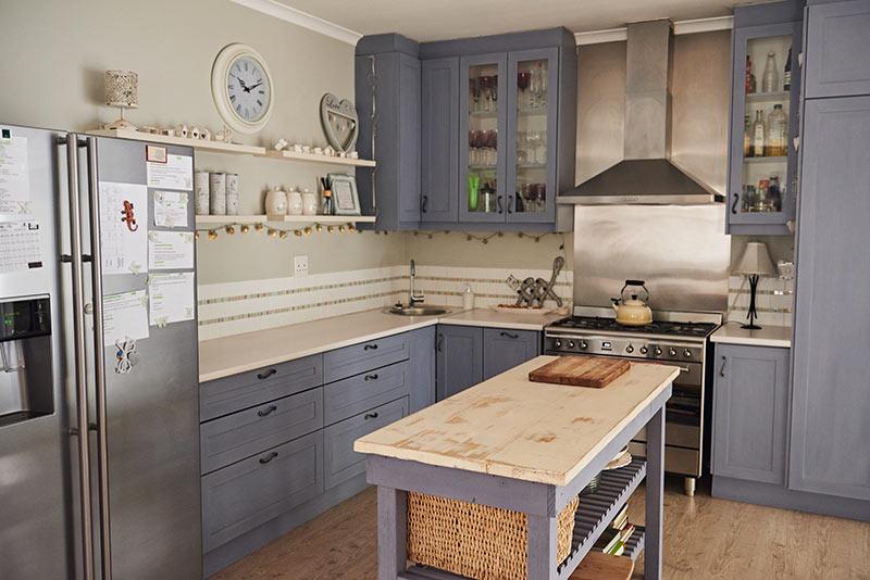 Piccola cucina angolare grigia con top in legno e piccola isola centrale.