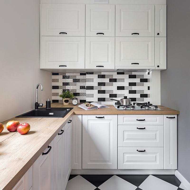 Piccolissima cucina bianca ad angolo con top in legno e piastrelle tipo mosaico bianco e nero.