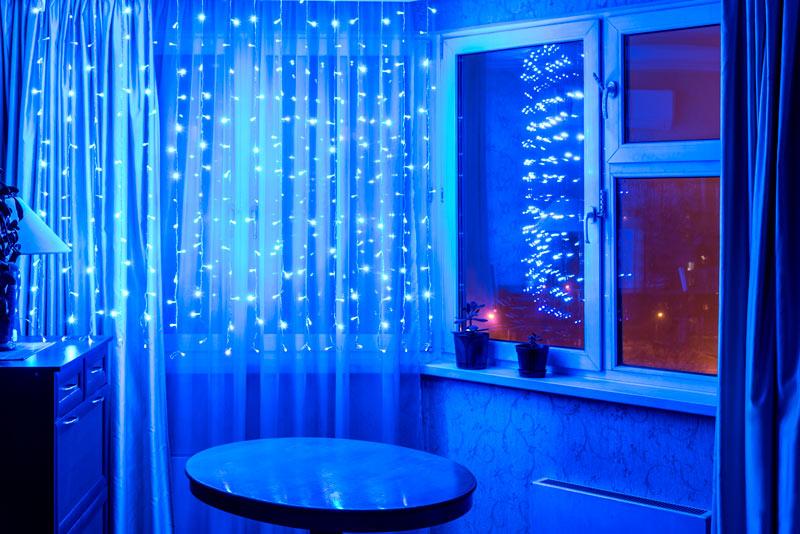 Tende illuminate con luci a LED blu in questo salotto.