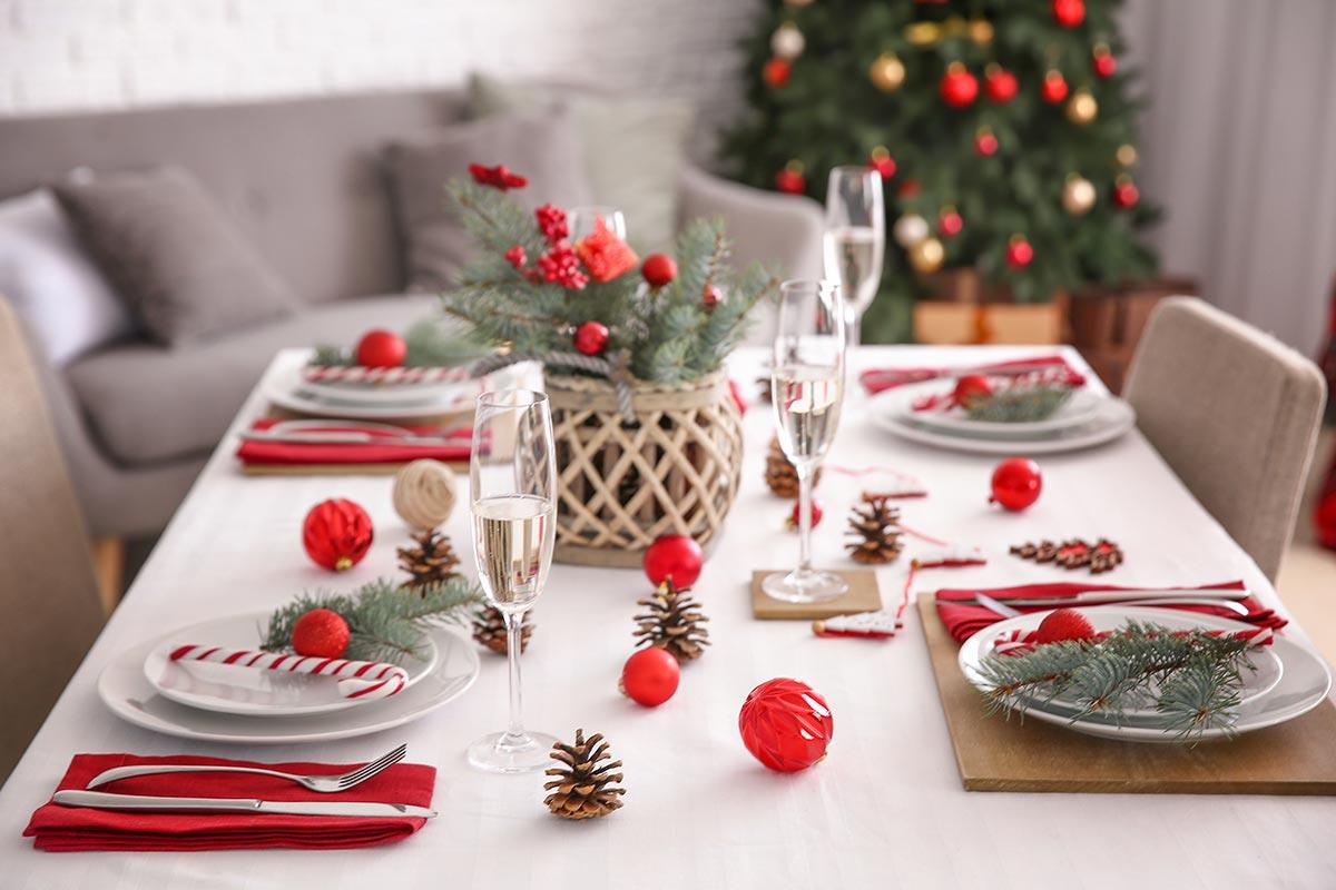Come addobbare la tavola di Natale con pigne e palline rosse.