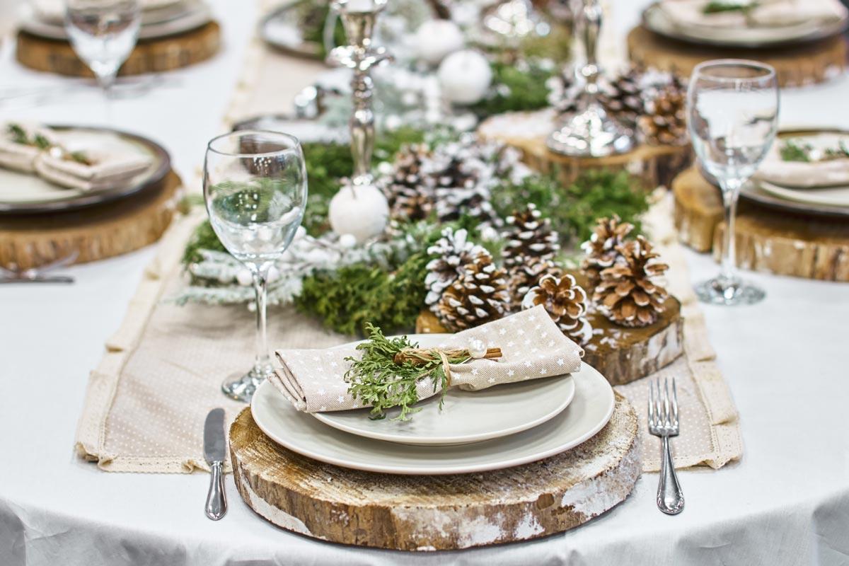 Decorare la tavola di Natale con un tronco come sotto piatto.
