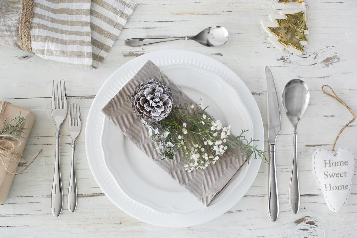 Decorare la tavola di Natale, piatto con pigne e fiori.