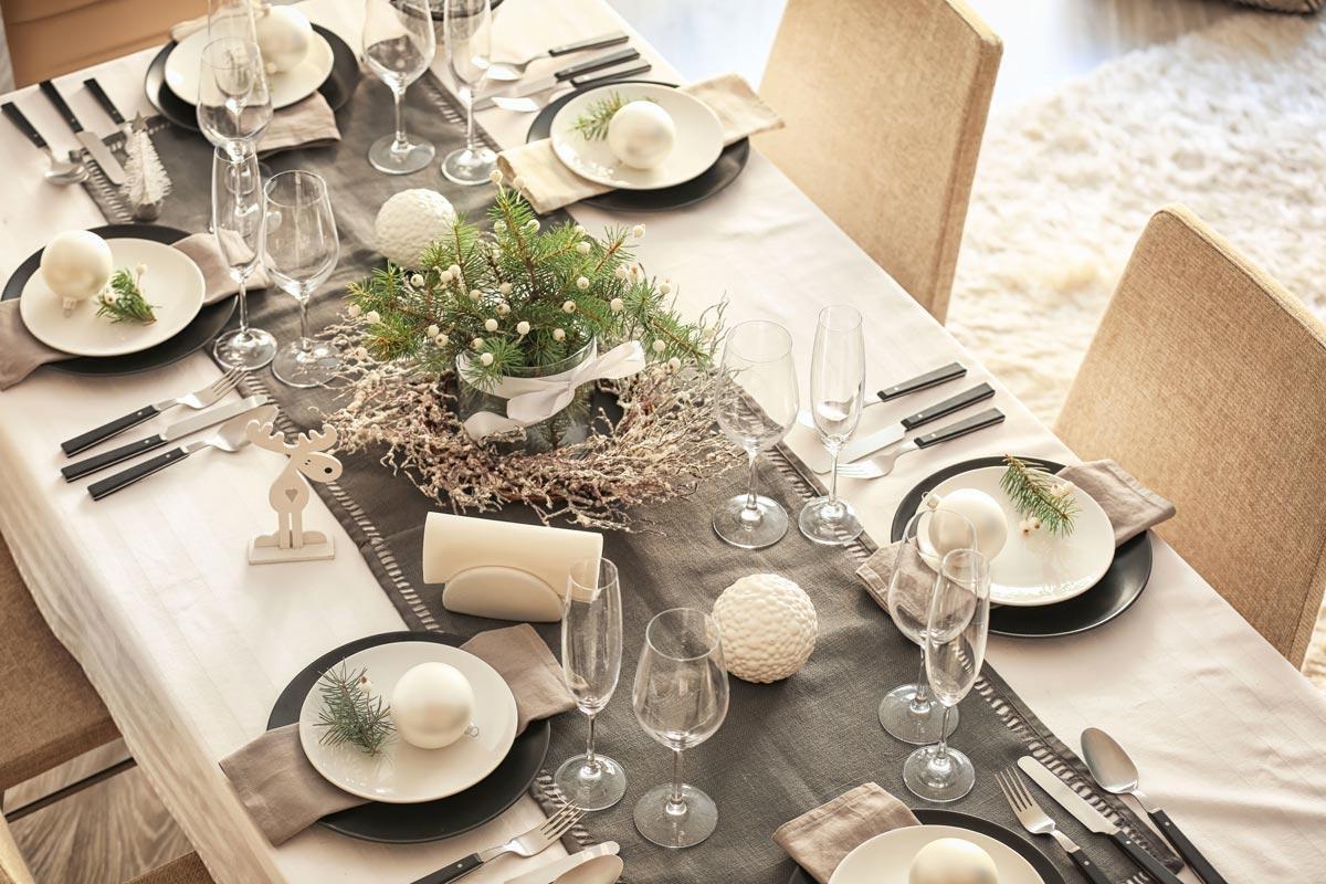 Decorare la tavola di Natale con rami di pino.
