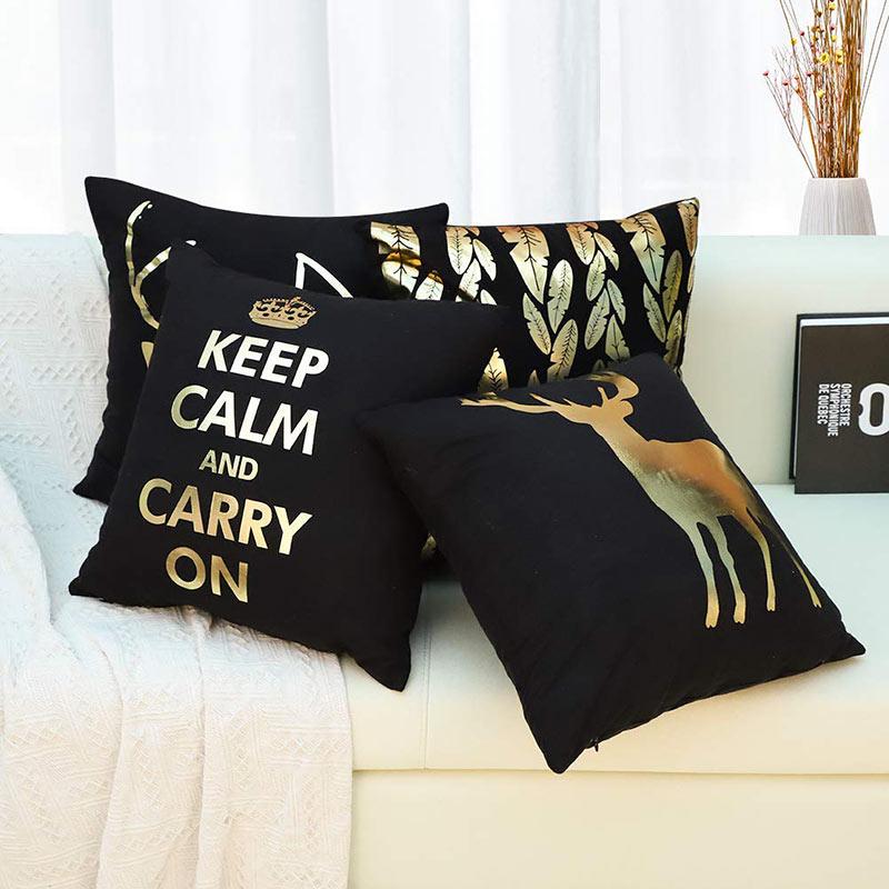 Le decorazioni natalizie per divano, cuscini neri con scritte oro.