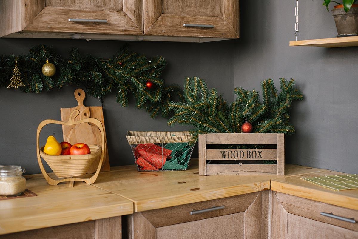 Cassetta di legno con finti rami di pino per decorare in cucina durante Natale.