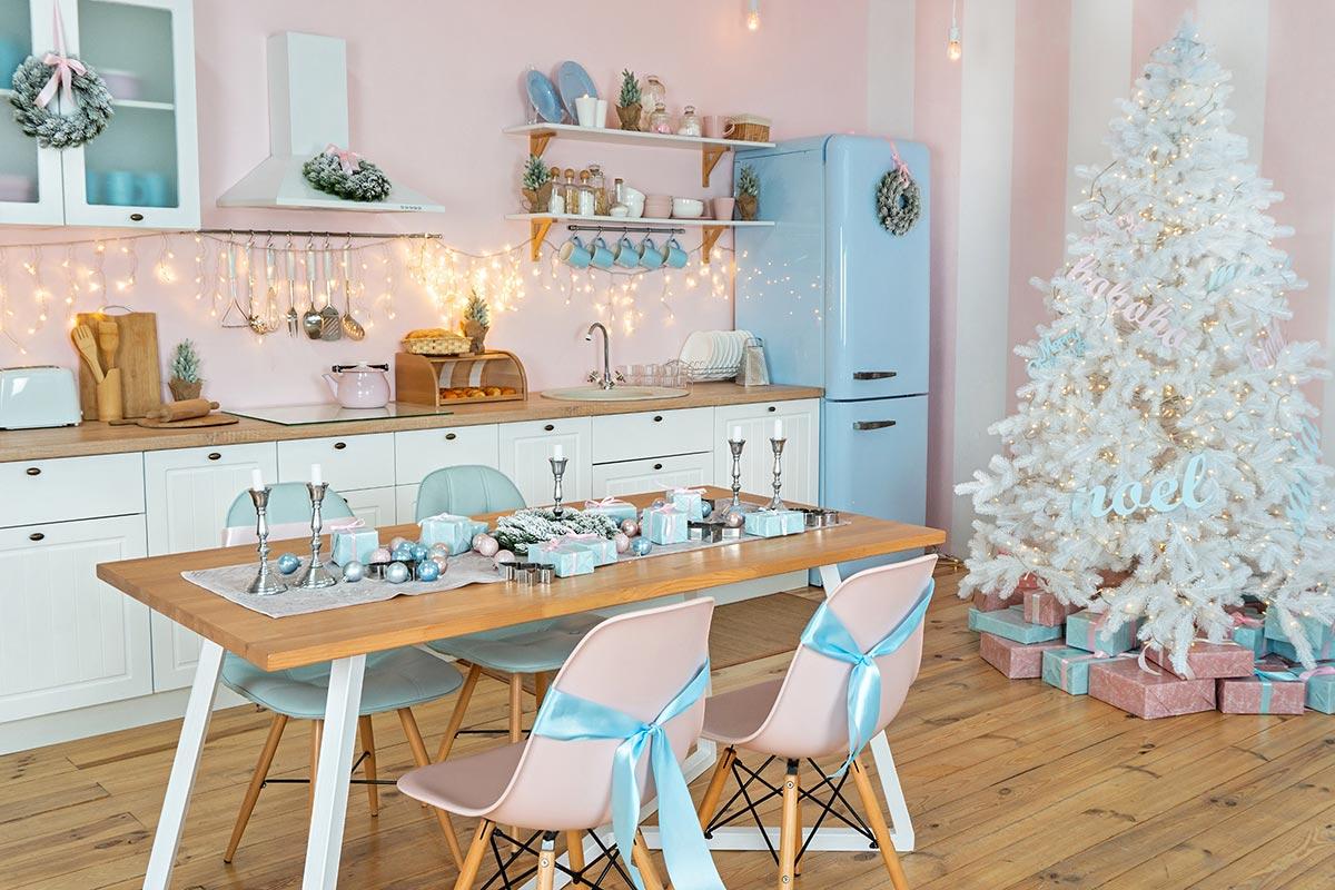 Bellissima cucina bianca e celestino con parete rosa tutta decorata per Natale.