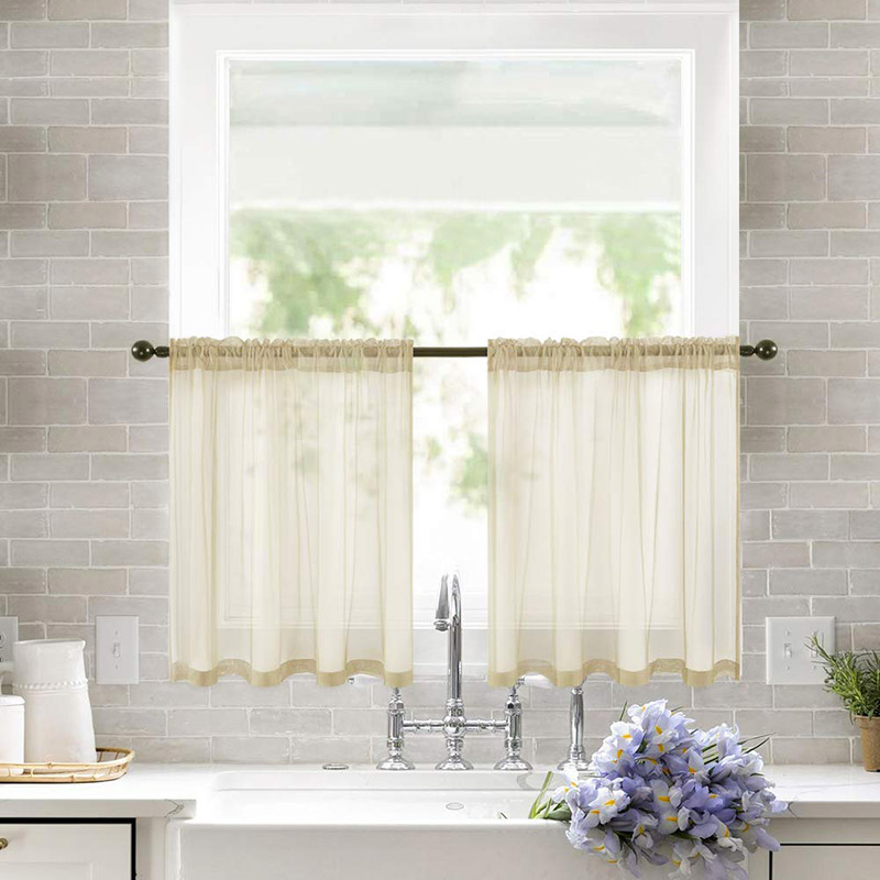 Tendina con mantovana beigne semi trasparente, sopra lavandino in cucina.