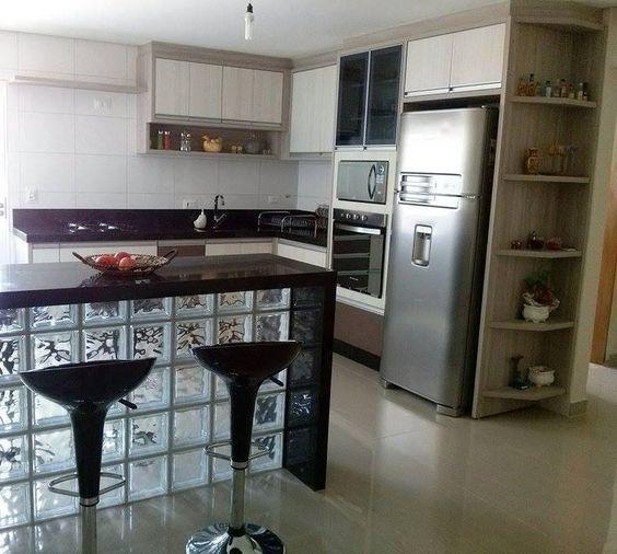 Penisola cucina in vetromattoni con top nero e due sgabelli.