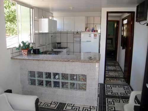 Penisola cucina in muratura con inserti in vetrocemento e top in marmo.
