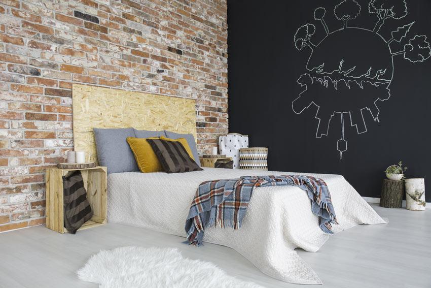 Camera da letto moderna con una parete con pittura lavagna e parete con mattoni a vista vintage.