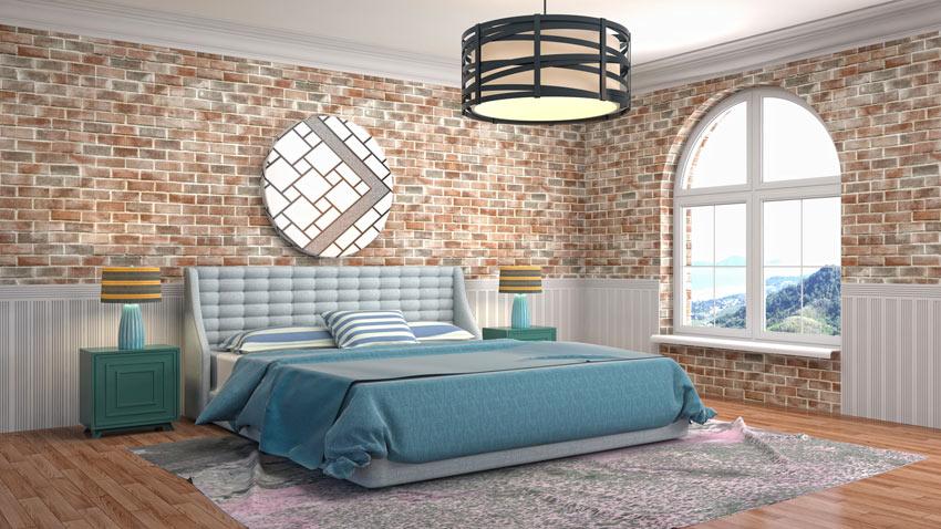 Grande camera da letto con pareti rivestite di mattoni rossi.