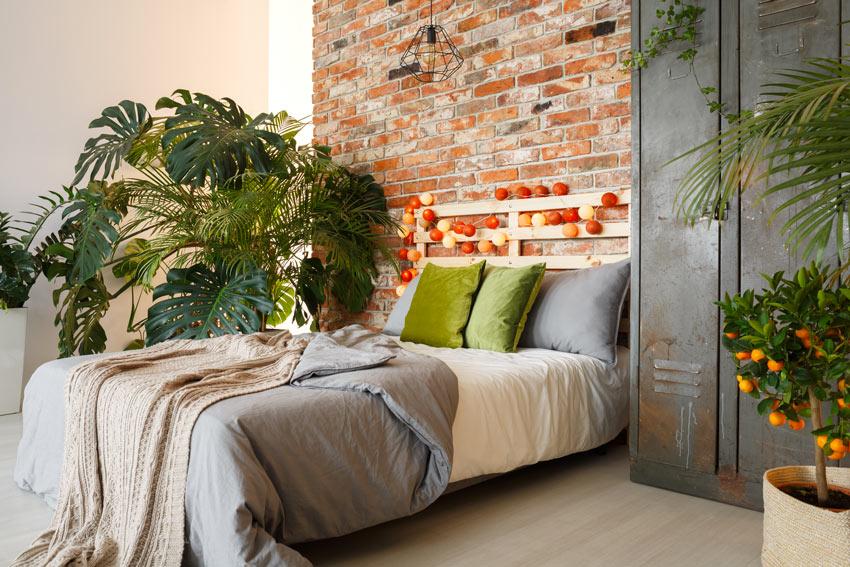 Letto con testiera in pallet di legno, parete con mattoni a vista, ideale per uno stile vintage.