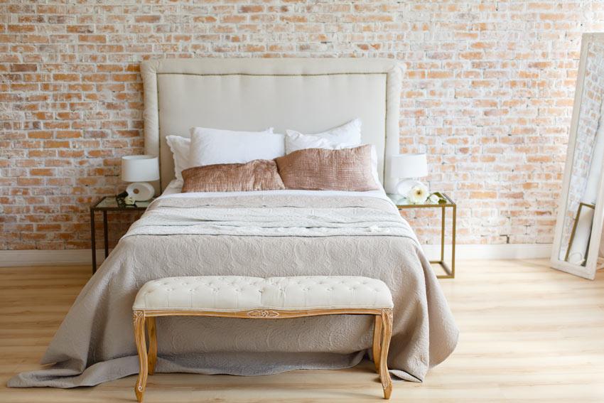 Camera con letto color tortora e pareti con mattoni a vista, un tocco vintage.
