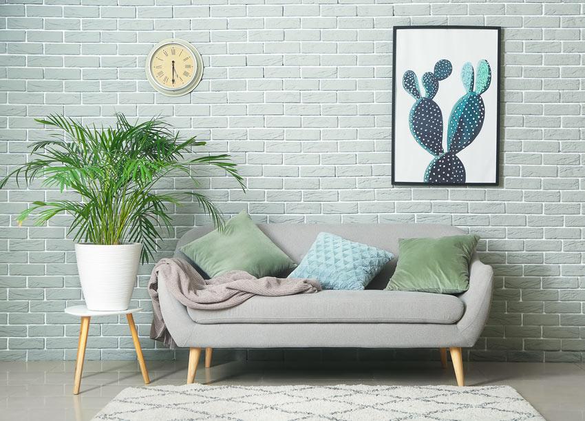Soggiorno con divano 3 posti con sgabello dove è appoggiato un vaso bianco con una bella pianta.
