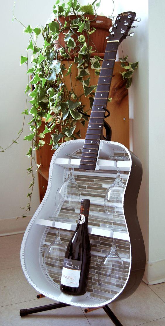 Una vecchia chitarra diventa un porta bicchieri con bottiglia di vino