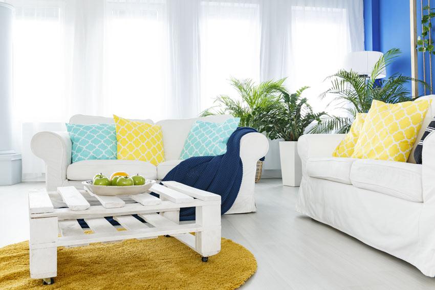 Soggiorno moderno bianco con cuscini colorati e tavolino in pallet.
