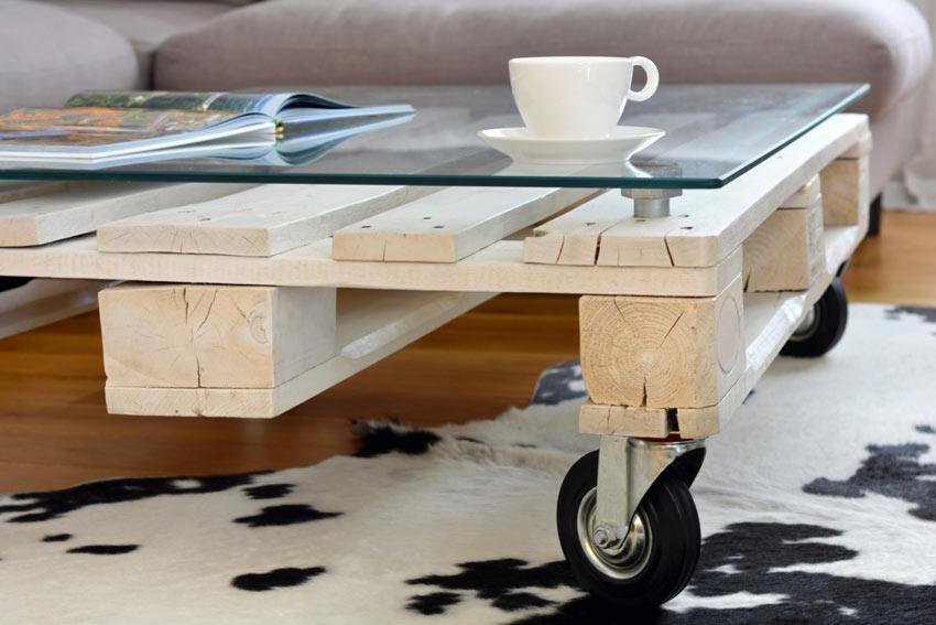 Tavolino fai da te con bancali e lastra di vetro più rotelle.