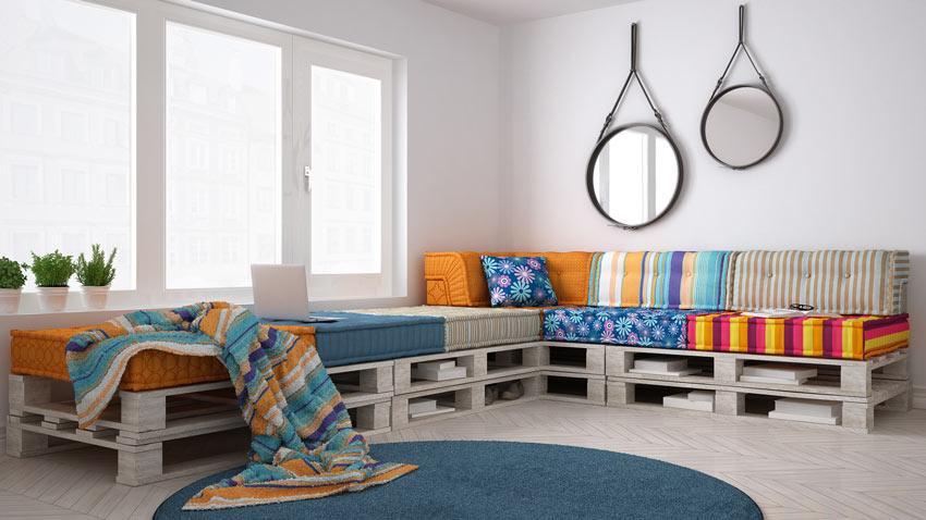 Grande divano angolare realizzato con dei pallet con cuscini colorati.
