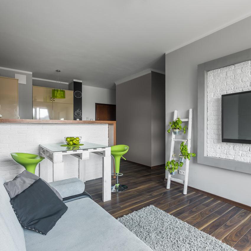 Soggiorno con cucina open space e tavolo realizzato con bancali e due sgabelli.