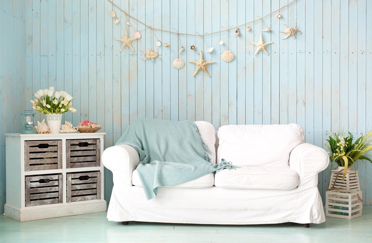 Salotto decorato in stile marino con conchiglie e stelle di mare appese.