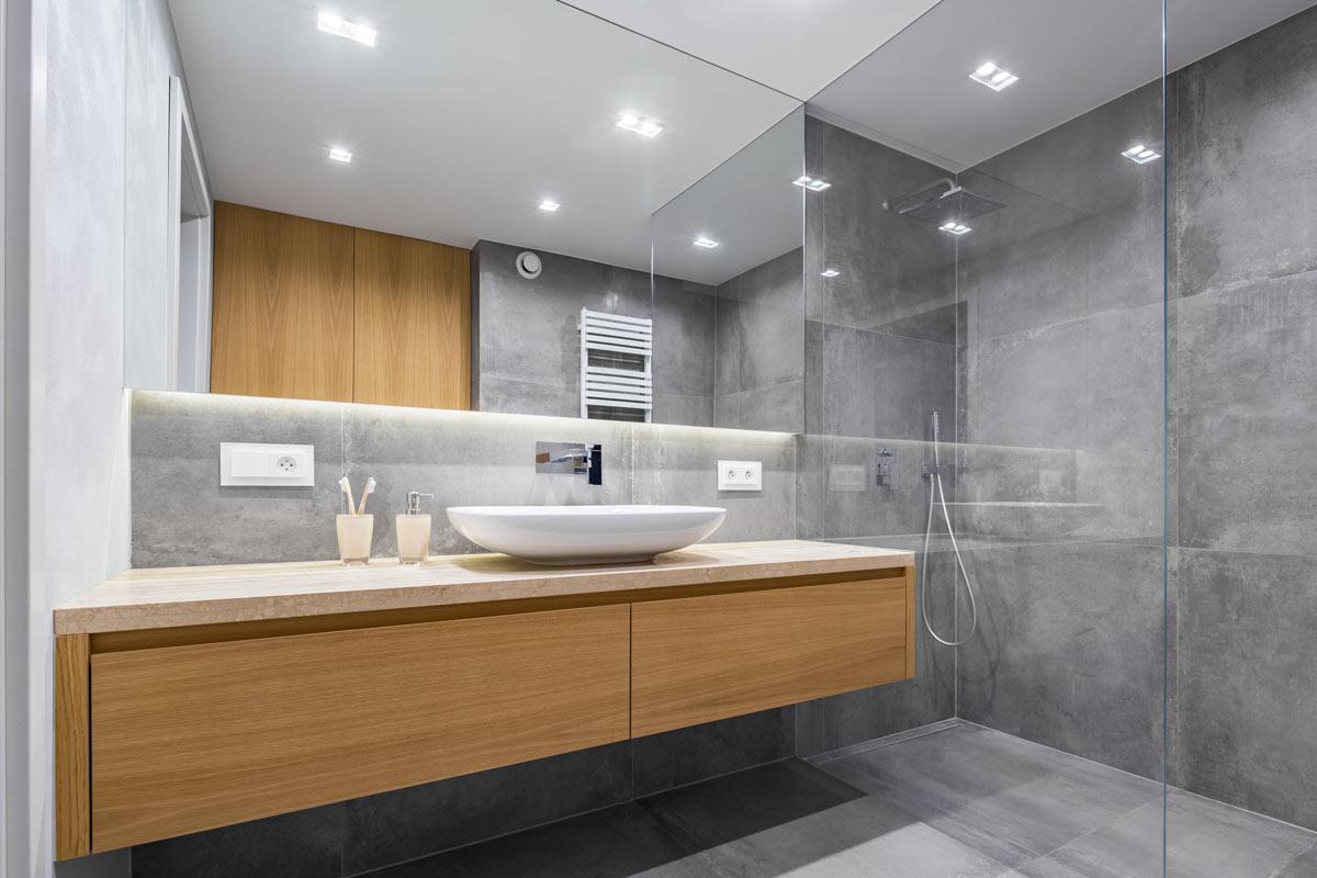 Bagno elegante grigio con mobile lavabo in legno.