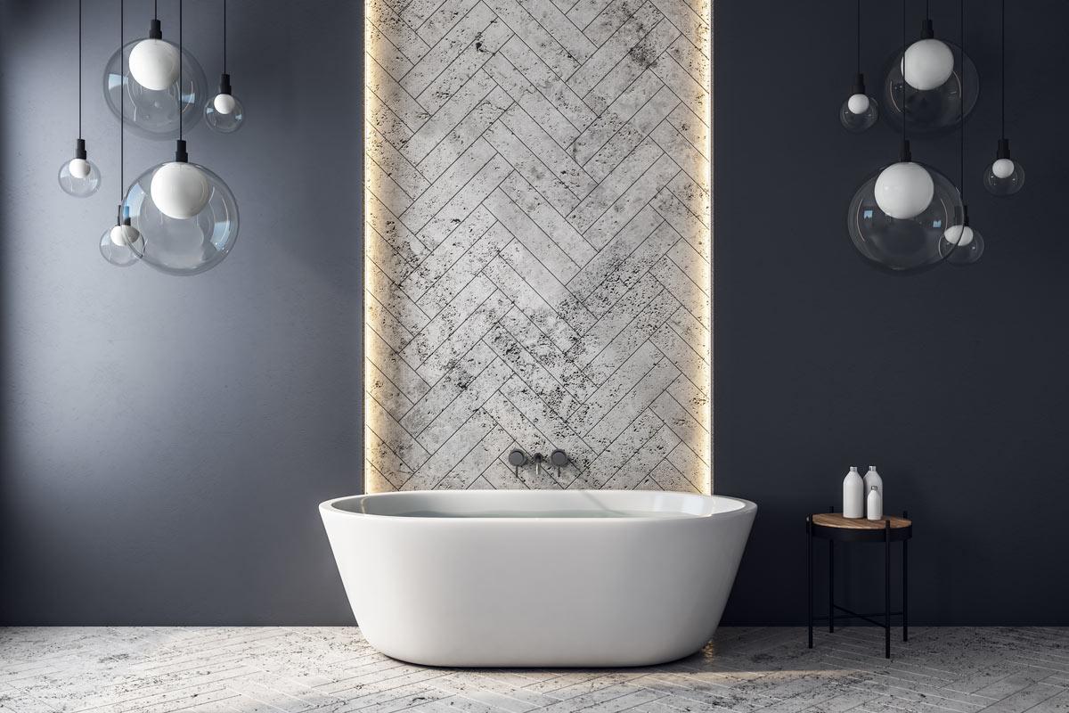 Bagno design con vasca da bagno e parete grigia spezzata con una strisce di piastrelle bianche a spina di pesce.