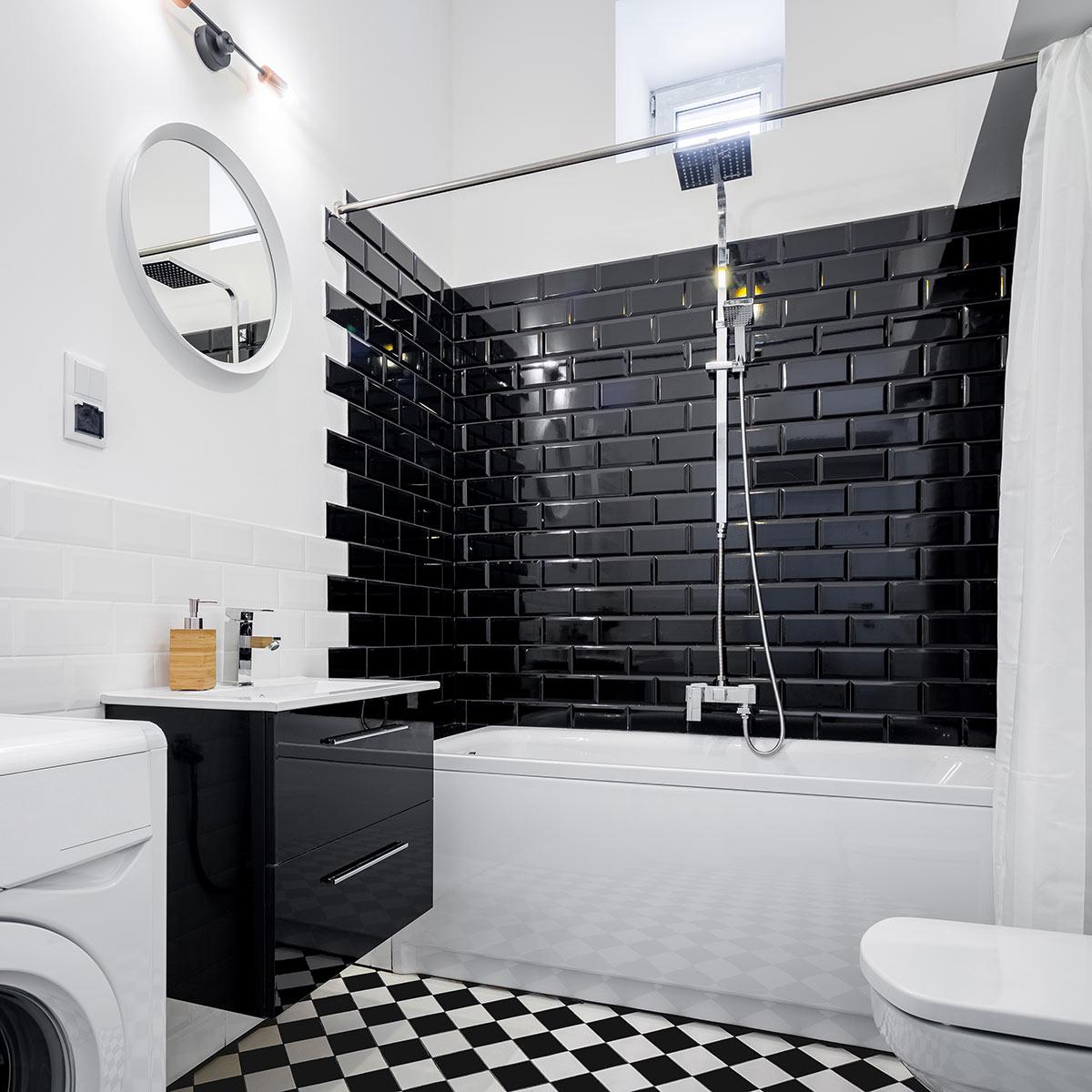 Bagno design con interno doccia rivestito con piastrelle nere effetto mattoncini.