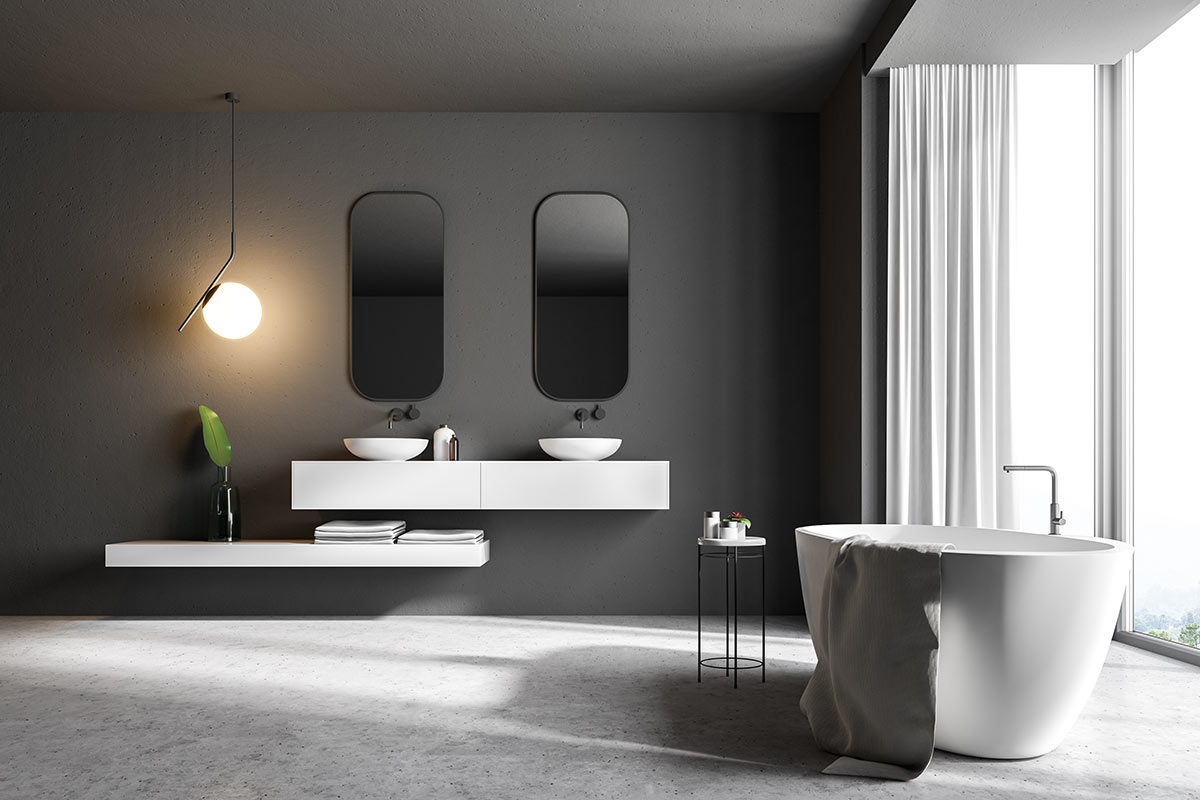Bagno contemporaneo con mobili e vasca nera e parete scura.