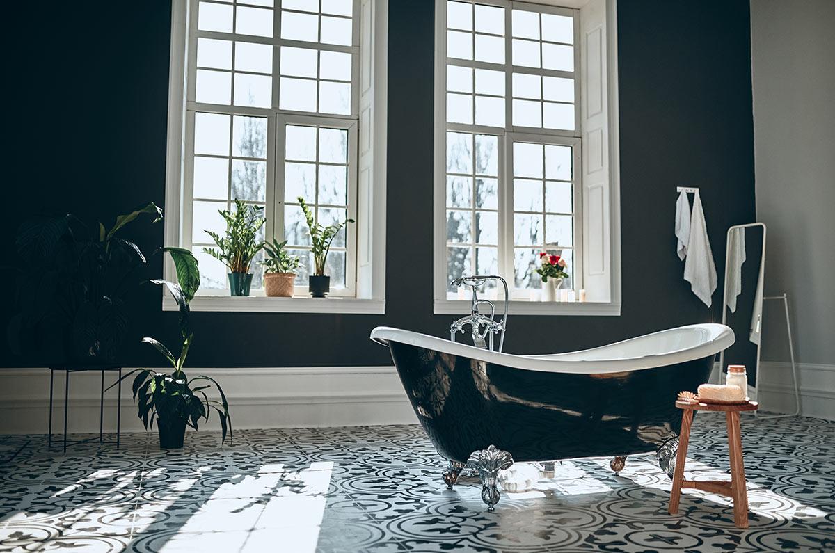 Bagno nero con vasca chic e pavimento bianco e nero.