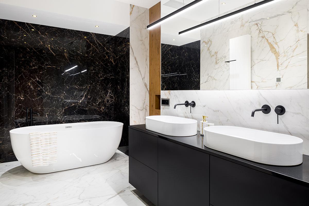 Bagno moderno bianco e nero con parete rivestite di marmo.