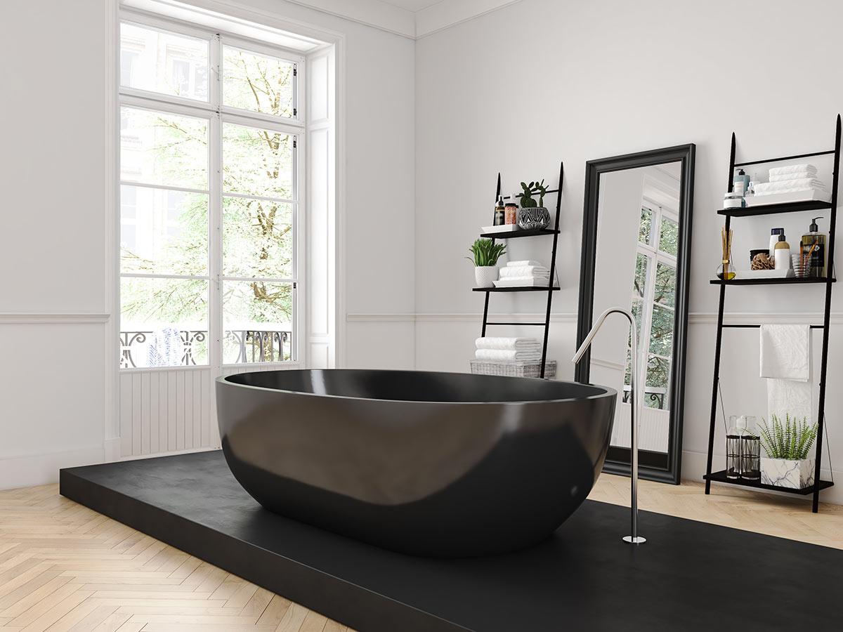Bagno con vasca nera e pavimento in legno a spina di pesce.
