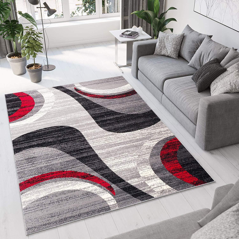 Salotto moderno con divano grigio e tappeto con forme geometriche grigio e rosso.