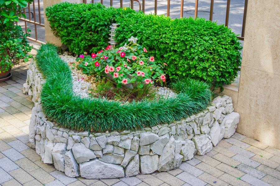 Aiuola fiorita con staccionata realizzata con le pietre.