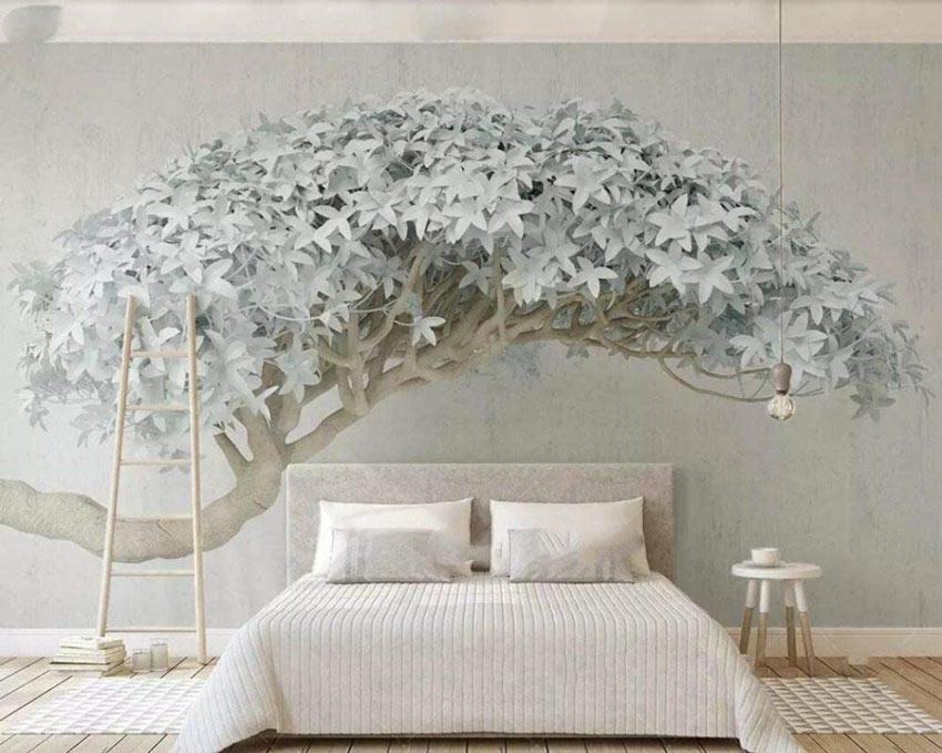 Carta da parati con il disegno di un albero sopra la testata de letto.