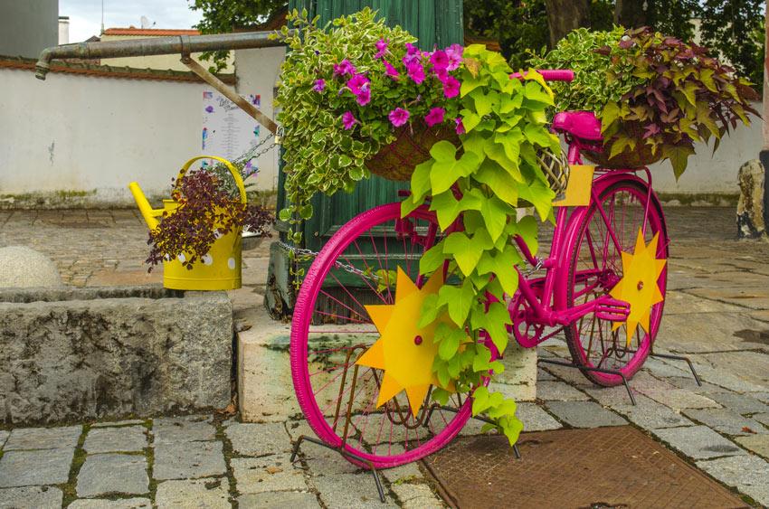 Vecchia bicicletta dipinta di fucsia e decorata con fiori.