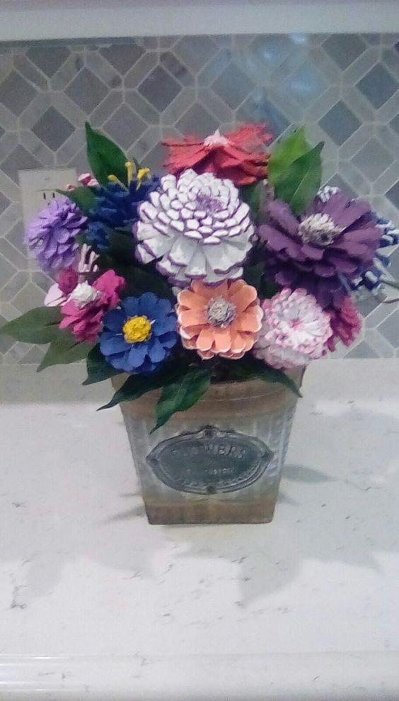 vaso con fiori finti realizzati con pigne colorate.