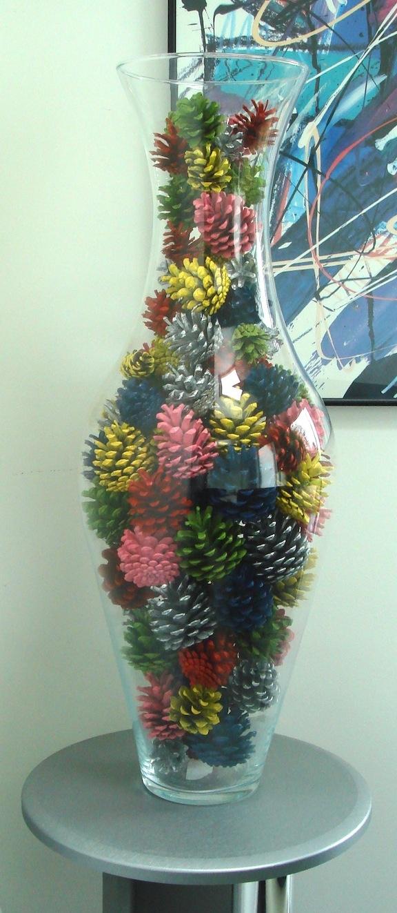 Un vaso di vetro riempito di pigne colorate.