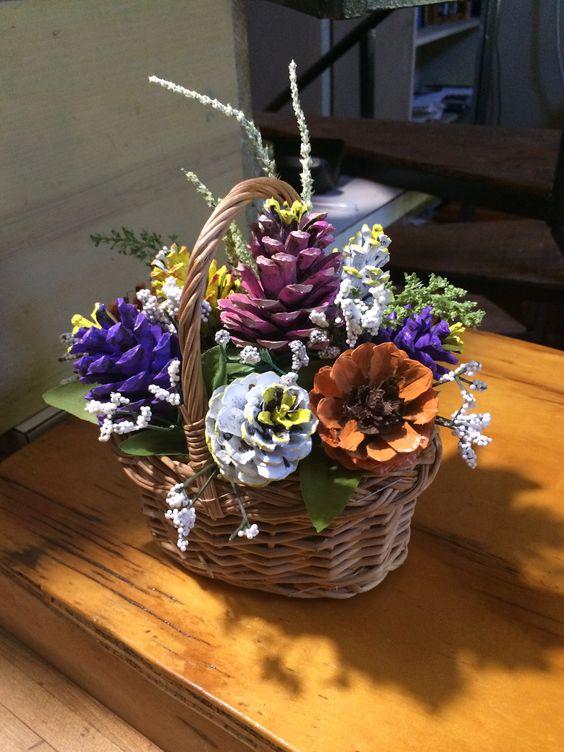Bellissimo vaso in vimini con pigne colorate che sembrano fiori.