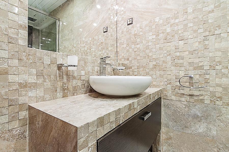 Bagno in muratura ristrutturato con piastrelle effetto pietra.