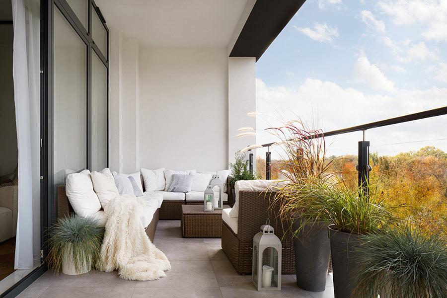 Balcone con divano da esterno ad angolo decorato con vasi di fiori.