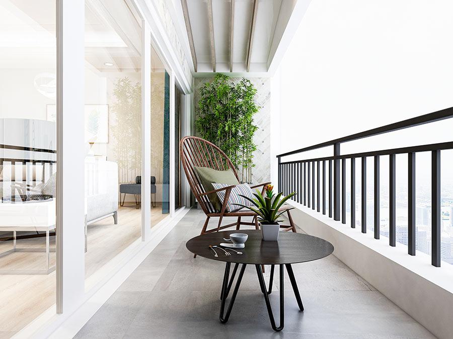 Bellissimo balcone lungo arredato con tavolino nero tondo e canne di bambou.