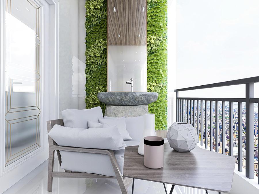 Bellissimo balcone con giardino verticale e salotto da esterno con cuscini bianchi.