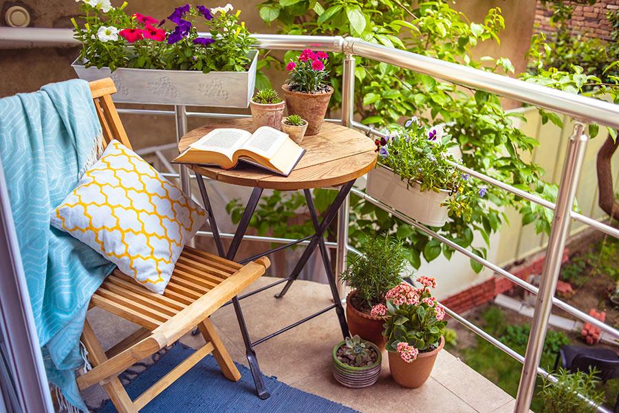Balcone fiorito arredato con tavolino tondo.