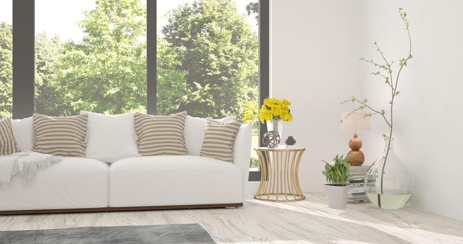 Soggiorno luminoso con divano bianco e cuscini a righe tortora, damigiana decorativa con ramo.