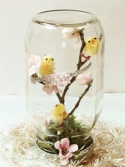 Barattolo di vetro con rami fioriti, ideale per una decorazione di pasqua fai da te.