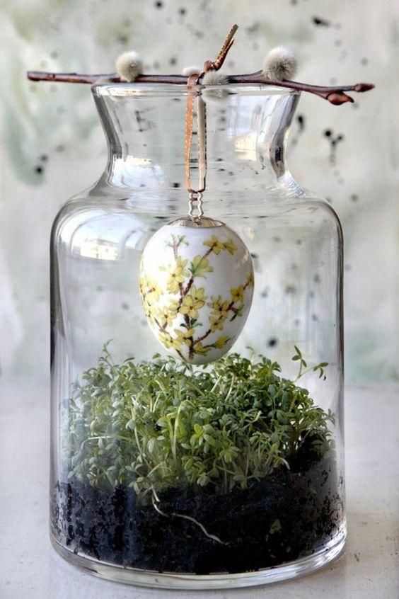 Piantina con un ovetto in un barattolo di vetro per decorare a pasqua.