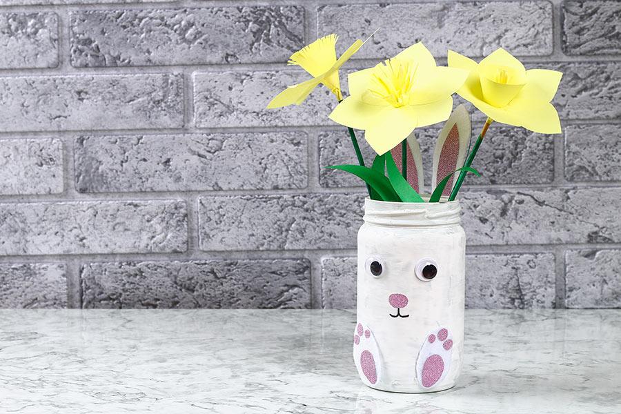 Vasetto di vetro con fiori decorato per la pasqua.